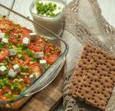 Bakade grönsaker - zucchini, morötter och tomater - med vit ost och klippt grönska i en glass maträtt på en träyttersida Royaltyfria Bilder