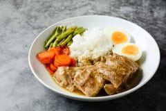 Bakade grisköttstöd med ris royaltyfria bilder