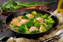 Bakade köttbullar av den fega filén med garnering med quinoaen och kokaad broccoli royaltyfri bild
