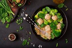 Bakade köttbullar av den fega filén med garnering med quinoaen och kokaad broccoli arkivfoto