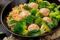 Bakade köttbullar av den fega filén med garnering med quinoaen och kokaad broccoli royaltyfri fotografi