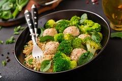 Bakade köttbullar av den fega filén med garnering med quinoaen och kokaad broccoli royaltyfria foton