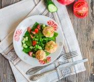 Bakade kikärtar klumpa ihop sig med sesam- och grönsaksallad på en grå färg Royaltyfri Bild