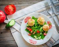 Bakade kikärtar klumpa ihop sig med sesam- och grönsaksallad på en grå färg Fotografering för Bildbyråer