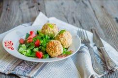 Bakade kikärtar klumpa ihop sig med sesam- och grönsaksallad på en grå färg Arkivfoton