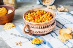 Bakade kikärtar med kryddor på lantlig bakgrund, rökt paprika Arkivfoto
