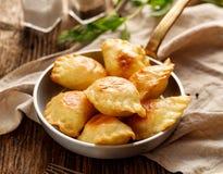 Bakade klimpar som är välfyllda med ostmassaost och potatisar i en panna arkivbild
