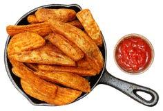Bakade kryddade potatiskilar i gjutjärnkastrull med ketchup Royaltyfria Bilder