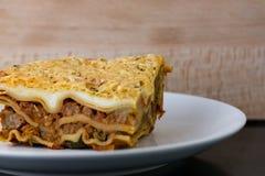Bakade lasagner på en vit platta med träbakgrunden Royaltyfri Fotografi