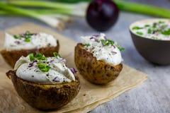 Bakade omslagspotatisar som är välfyllda med ostmassa- och vårlöken royaltyfria bilder