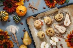 Bakade päron och äpplen på den stekheta pannan med kryddor, små pumpor och blommor omkring på grå färgtabellen Royaltyfri Bild