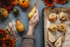 Bakade päron och äpplen på den stekheta pannan med kryddor, små pumpor och blommor omkring på grå färgtabellen Royaltyfria Foton