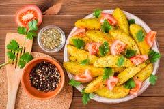 Bakade potatisar i en peel med tomater, örter, kryddor och sesam royaltyfri fotografi