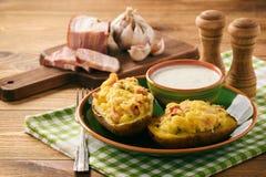 Bakade potatisar med bacon, ost och persilja arkivbild
