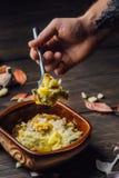 Bakade potatisar med kött som doppas i ost i lerabruntdisk på en träbakgrund royaltyfria bilder