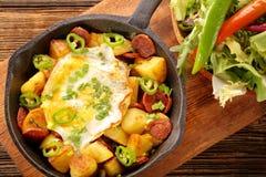 Bakade potatisar med korvchorizoen och det stekte ägget på stekpannan royaltyfri foto