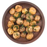 Bakade potatisar med kryddor i en keramisk platta royaltyfri fotografi