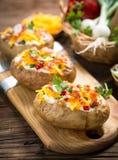 Bakade potatisar med ost och bacon arkivbilder