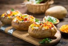 Bakade potatisar med ost och bacon royaltyfria bilder