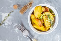 Bakade potatisar med rosmarin och salladslökar i vitt keramiskt f Arkivfoton