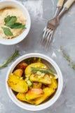 Bakade potatisar med rosmarin och salladslökar i vitt keramiskt f Arkivbilder