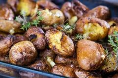 Bakade potatisar som är hela i deras hudar med timjanrosmarin och vitlök royaltyfria bilder
