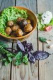 Bakade potatisar som är hela i deras hudar med tomater rosmarin och vitlök arkivbilder