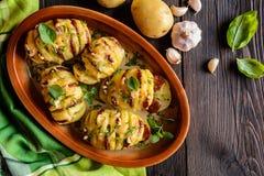 Bakade potatisar som är välfyllda med korven, ost, vitlök och örter arkivfoton