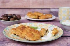Bakade potatisköttbullar klumpa ihop sig i en gul platta Tillbaka oliv och yoghurtsås Closeup nya signaler Wood bakgrund royaltyfria foton