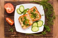 Bakade smörgåsar med tomaten, ost och gräsplaner och skivade grönsaker Arkivfoto