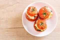 bakade tomater som är välfyllda med ost och spenat Arkivfoton