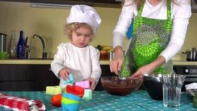 Bakar blandande deg för modern och för dottern tillsammans och förbereda sig för muffin arkivfilmer