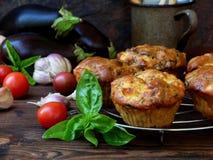 Bakar ihop välsmakande muffin för mellanmål med aubergine, tomater, basilika och ost på träbakgrund Fotografering för Bildbyråer