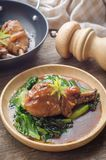 Bakat fegt ben med grönsaker och sås på lantlig träbac Royaltyfri Foto