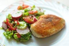 Bakat fegt bröst med grönsaksallad på en vit platta Royaltyfria Foton