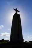 Bakbelyst bild med konturn av den berömda Cristoen-Rei eller Konung-Kristus fristaden i Almada Arkivbilder