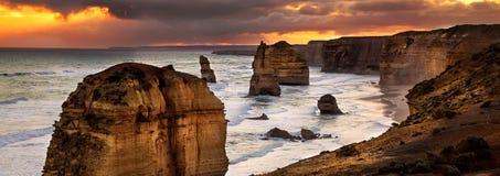 Bakbelyst guld- solnedgång för 12 apostlar Arkivbild