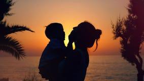 Bakbelyst pojke och hans moder som kramar på den marin- solnedgången stock video