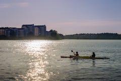 Bakbelyst solnedgångsikt av ett par som kanotar i staden Royaltyfria Bilder