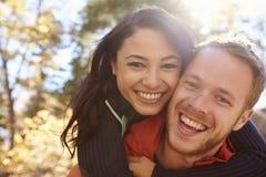 Bakbelyst stående av par för blandat lopp som omfamnar i en skog royaltyfri foto