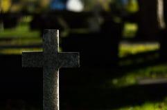 Bakbelyst stenkors i en kyrkogård royaltyfri fotografi