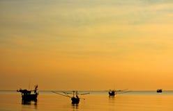 Bakbelysta fiskebåtar på havet royaltyfri fotografi