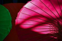 Bakbelysta rosa paraplyvisningstöd och färg royaltyfri bild