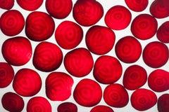 Bakbelysta skivor av rödbeta, gör sammandrag texturerad bakgrund Arkivfoto