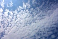 Bakbelysta vadderade moln arkivfoton