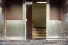 Bakdörr eller tillbaka ingång av en byggnad med metalllogi Royaltyfri Foto