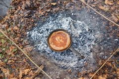 We bake bread from the dough in a pan on the coals of the fire stock image