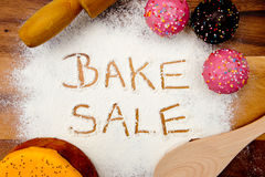 Bake Sale with cake. Written in flour Royalty Free Stock Image