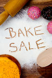 Bake Sale with cake. Written in flour Stock Photography