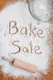 Bake Sale Poster. Flour on a wooden table symbolising a Bake Sale Notice Stock Photo